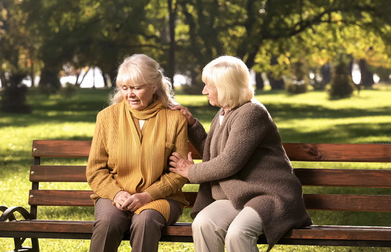 Senior lady comforting old friend about her loss, sitting on bench in park